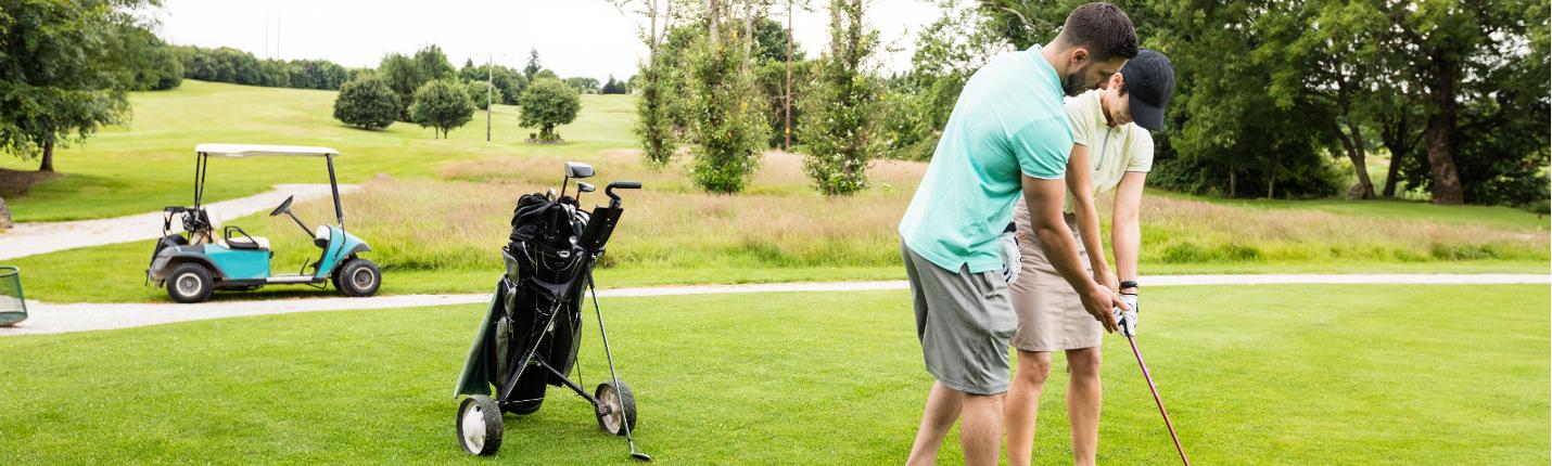 Golftrainer mit Schüler